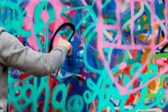 Closeup arm of young guy drawing colorful graffiti on the wall. Concept  contemporary culture Royalty Free Stock Photography