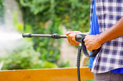 Closeup arms of man wearing square pattern blue and white shirt holding high pressure water gun, pointing towards green garden Stock Photos