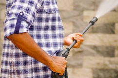 Closeup arms of man wearing square pattern blue and white shirt holding high pressure water gun, pointing towards grey brick wall Royalty Free Stock Photos