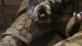 Cigarette in army soldiers` trembling hands. Closeup of army soldier trembling hands holding cigarette and smoking after hard battle. Military soldier suffering stock video footage