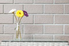Closeup artificial colorful flower on transparent glass bottle on wood weave table on blurred brown brick wall texture background. Closeup artificial flower on stock photography