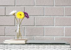 Closeup artificial colorful flower on transparent glass bottle on wood weave table on blurred brown brick wall texture background. Closeup artificial colorful stock photography