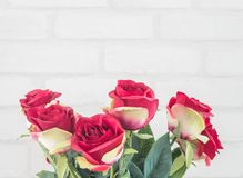 Closeup artificial fabric red rose flower for decorate on white brick wall textured background with copy space Stock Image