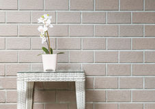 Closeup artificial plant with white orchid flower on pink flower pot on wood weave table on blurred brown brick wall texture backg Stock Photography