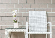 Closeup artificial plant with white orchid flower on pink flower pot on wood weave table with wood weave chair on blurred brown br Royalty Free Stock Image