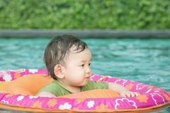 Closeup a asian baby boy sit in a boat for children in the swimming pool background. Closeup asian baby boy sit in a boat for children in the swimming pool royalty free stock images