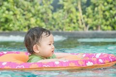 Closeup a asian baby boy sit in a boat for children in the swimming pool background. Closeup asian baby boy sit in a boat for children in the swimming pool royalty free stock image
