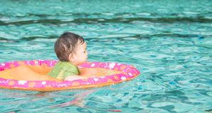 Closeup a asian baby boy sit in a boat for children in the swimming pool background. Closeup asian baby boy sit in a boat for children in the swimming pool stock image
