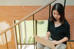 Closeup Asian beautiful woman Wearing a black shirt Sitting in the stairs in the house Use a laptop computer to work happily stock photography