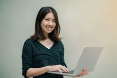 Closeup Asian beautiful woman Wearing a black shirt standing around the gray wall Use a laptop computer to work happily royalty free stock photo