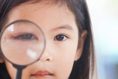 Closeup of asian child girl eye swell from bacteria virus. Looking through a magnifying glass Stock Image