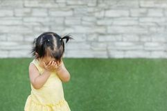 Closeup asian girl take her hands off the face and play hidden with someone on grass floor and brick wall textured background with royalty free stock photos