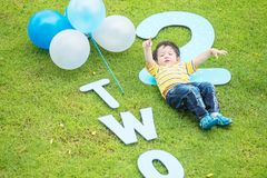 Closeup happy asian kid lie on grass floor in park textured background in 2 nd years anniversary concept. Closeup asian kid lie on grass floor in park textured Royalty Free Stock Image