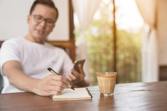 Closeup asian male hand is writing a note in a cafe,Choose a foc. Al point at the hands of men Stock Photos