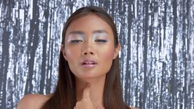 Thai asian model in studio with silver rain disco background and party makeup. Closeup asian model wears party look poses to a camera. Silver rain background stock video
