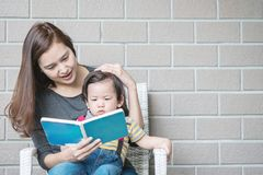 Closeup asian mother is teaching her son to read a book on stone Royalty Free Stock Photo