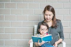 Closeup asian mother is teaching her son to read a book on stone Royalty Free Stock Photography