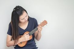 Closeup asian woman playing ukulele on white cement wall texture background with copy space stock images
