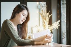 Closeup asian woman reading a book at the wooden counter desk in coffee shop with smile face in happy motion on blurred coffee sho. P background Royalty Free Stock Image