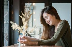 Closeup asian woman reading a book at the wooden counter desk in coffee shop with smile face in happy motion royalty free stock images