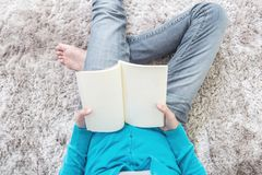 Closeup asian woman sitting on gray carpet at floor in the house textured background for read a book in relax time , free time at Royalty Free Stock Photo