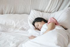 Closeup asian woman sleep on bed under blanket in bedroom background in the morning stock photo