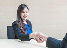 Closeup asian woman success to deal business with someone with happy face in meeting room on blurred wooden desk and wall textured Royalty Free Stock Photo