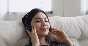 Closeup asian woman wear headphones closed eyes enjoy favourite music