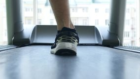 Closeup of athlete`s feet running on treadmill stock video