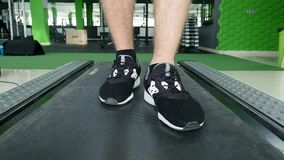 Closeup of athlete`s feet running on treadmill stock video footage