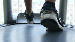 Closeup of athlete`s feet running on treadmill stock footage