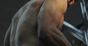 Closeup athletic black male training with cable sport simulator in gym workout. stock video