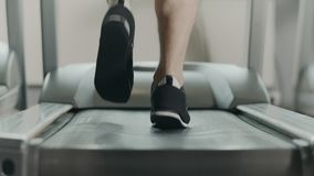 Closeup athletic feet running on treadmill in fitness gym. Back view of black shoes having workout on treadmill. Low view sneakers training in sport club stock footage