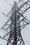 Closeup atmospheric photo of the high voltage transmission tower standing on the gray sky background after blizzard Stock Photography