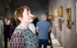 Closeup on attentive senior woman visiting museum and enjoying a stock photography