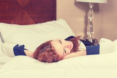 Closeup attractive happy female relaxing on her bed Stock Photos