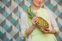 Closeup of attractive woman with pineapple. Closeup of attractive women with pineapple smile on a blue background. Happy girl hold ananas ready to make juice Royalty Free Stock Image