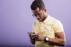 Young happy african man with cellphone  on lilac background stock image