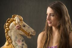 Portrait of young woman and antique carousel horse. Closeup of attractive young woman in lavender dress with an antique carousel horse Stock Photos