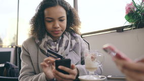 Closeup of Attrcative mixed race woman using credit card shopping online with smartphone in street cafe while have stock video footage