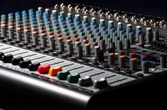 Closeup of an audio sound mixer. Against dark background stock photo