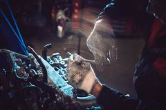 Closeup of an auto mechanic working on a car engine. Closeup of an auto mechanic working on an automobile engine. Installing the intake manifold on the opposing stock image