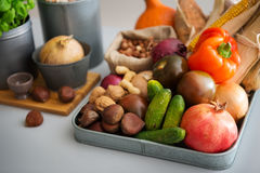Closeup of Autumn fruits, vegetables, nuts on kitchen counter. A metal tray is filled with autumn fruits, nuts, vegetables, and grains. The house will soon be Stock Photography