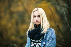 Closeup autumn portrait of young serious blonde woman in scarf and jeans jacket Stock Photography
