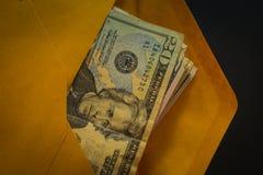 Closeup av åtskilliga US dollar i brunt kuvert Royaltyfria Bilder