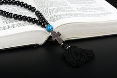 Closeup av öppnade helig bibel- och radbandpärlor med korset på svart bakgrund religion för bokbegreppskors Cyrillic text arkivfoton