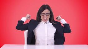Closeup av affärskvinnan i en affärsdräkt Hon sitter bak ett skrivbord och skriker på slaven som vinkar hans armar Rött stock video