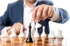 Closeup av affärsmannen som spelar schack och slår svart konung Royaltyfri Foto
