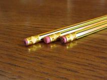 Closeup av använda blyertspennaradergummin på trätabellen Royaltyfri Bild