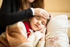 Closeup av att att bry sig det hållande huvudet för moder på den sjuka dotterpannan Royaltyfria Bilder